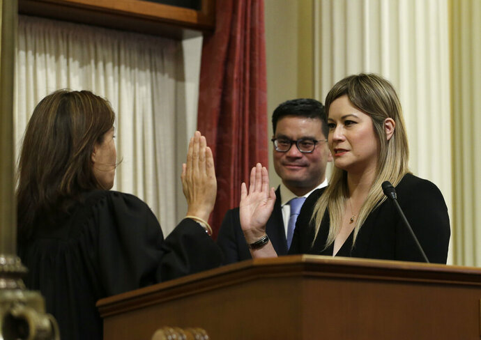 FILE — In this June 25, 2018 file photo Republican Ling Ling Chang, right, is sworn in to the California Senate by California Supreme Court Chief Justice Tani Cantil-Sakauye, as Chang's husband, Andrew Wong looks on in Sacramento, Calif. Chang announced Thursday, Nov. 21, 2019, that she will introduce legislation in January to make it a crime to send unwanted nude photos to people online or in text messages. (AP Photo/Rich Pedroncelli, File)