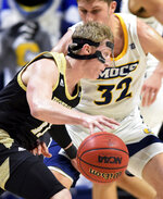 Wofford's Ryan Larson (11) dribbles past Chattanooga's Matt Ryan (32) during an NCAA college basketball game Wednesday, Jan. 15, 2020, in Chattanooga, Tenn. (Robin Rudd/Chattanooga Times Free Press via AP)