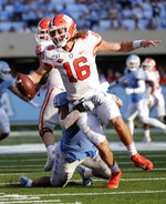Clemson quarterback Trevor Lawrence (16) is pressured by North Carolina's Chazz Surratt (21) during the third quarter of an NCAA college football game in Chapel Hill, N.C., Saturday, Sept. 28, 2019. (AP Photo/Chris Seward)