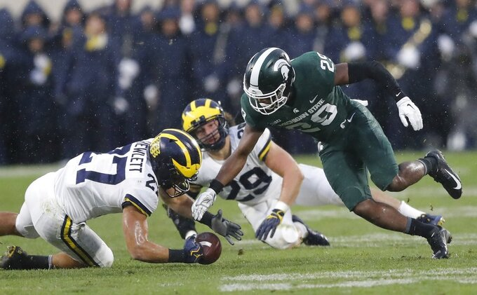 Michigan State punt returner Shakur Brown (29) fumbles as Michigan's Joe Hewlett (27) recovers during the second half of an NCAA college football game, Saturday, Oct. 20, 2018, in East Lansing, Mich. (AP Photo/Carlos Osorio)