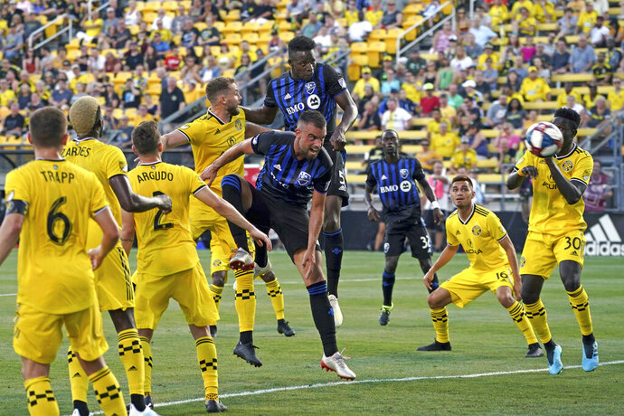 Montreal Impact's Zakaria Diallo, middle back, scores a goal as Rudy Camacho, middle, leaps against Columbus Crew's Josh Williams, back, during the first half of an MLS soccer match, Saturday, July 20, 2019, in Columbus, Ohio. (AP Photo/Aaron Doster)