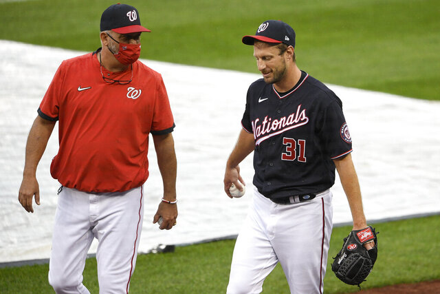 Washington Nationals starting pitcher Max Scherzer (31) walks on the field next to pitching coach Paul Menhart, left, before a baseball game against the New York Mets, Friday, Sept. 25, 2020, in Washington. The game was postponed due to inclement weather. (AP Photo/Nick Wass)