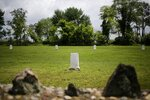 FILE - In this May 23, 2018, file photo, white markers, each indicating a mass grave of 150 people, are displayed on Hart Island in New York. The island has served as New York City's potter's field for 150 years, where part of the graveyard along the island's shoreline is gradually washing away. (AP Photo/Seth Wenig, File)