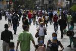 People wearing masks amid the new coronavirus pandemic walk on Sabana Grande boulevard in Caracas, Venezuela, Wednesday, June 17, 2020. (AP Photo/Matias Delacroix)