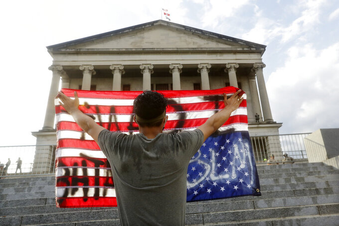 A man holds a flag upside down in front of the State Capitol during a peaceful protest Thursday, June 4, 2020, in Nashville, Tenn., over the death of George Floyd, who died May 25 after being restrained by police in Minneapolis. (AP Photo/Mark Humphrey)
