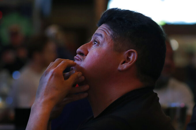 Chicago resident Frank Robelli reacts while watching one the many television screens at Lottie's Pub in Chicago's Bucktown neighborhood on Saturday, March 13, 2021. Bars and restaurants that were shuttered for months due to the pandemic have reopened their doors just in time for the NCAA basketball tournament. (AP Photo/Shafkat Anowar)