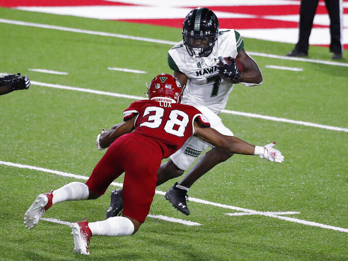 Hawaii running back Calvin Turner (7) tries to elude Fresno State defensive back Bralyn Lux during the second half of an NCAA college football game in Fresno, Calif., Saturday, Oct. 24, 2020. (AP Photo/Gary Kazanjian)