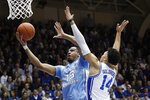 North Carolina forward Garrison Brooks (15) drives to the basket whiule Duke guard Jordan Goldwire (14) defends during the first half of an NCAA college basketball game in Durham, N.C., Saturday, March 7, 2020. (AP Photo/Gerry Broome)