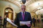 Senate Majority Leader Chuck Schumer, D-N.Y., looks over his notes as he talks to reporters about his plans for a procedural vote tomorrow on the bipartisan infrastructure deal senators brokered with President Joe Biden, at the Capitol in Washington, Tuesday, July 20, 2021. (AP Photo/J. Scott Applewhite)