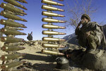 Afghan anti-al-Qaida fighters rest at a former al-Qaida base in the White Mountains near Tora Bora Wednesday Dec. 19, 2001, behind a string of ammunition found after the retreat of al-Qaida members from the area. (AP Photo/David Guttenfelder)