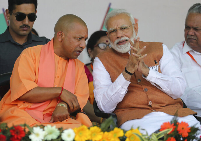 "FILE- In this March 28, 2019, file photo, Indian Prime Minister Narendra Modi, right, speaks with Chief Minister of Uttar Pradesh state Yogi Adityanath during an election campaign rally in Meerut, India. India's ruling Hindu nationalist party has approved legislation in Uttar Pradesh, the country's most populous state, that lays out a prison term of up to 10 years for anyone found guilty of using marriage to force someone to change religion. The decree was passed Tuesday and follows a campaign by Modi's Hindu-nationalist Bharatiya Janata Party against interfaith marriages. The party describes such marriages as ""love jihad,"" an unproven conspiracy theory used by its leaders and Hindu hard-line groups to accuse Muslim men of converting Hindu women by marriage. (AP Photo/Altaf Qadri, File)"