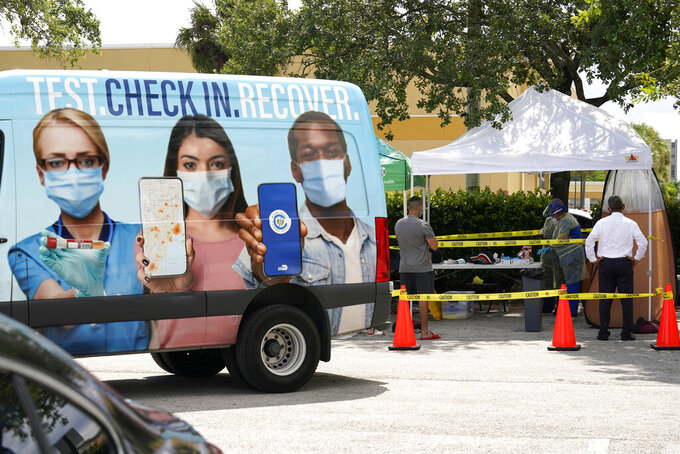 People wait in line at a Miami-Dade County COVID-19 testing site, Monday, July 26, 2021, in Hialeah, Fla. Florida accounted for a fifth of the nation's new infections last week, more than any other state, according to the U.S. Centers for Disease Control and Prevention. (AP Photo/Lynne Sladky)