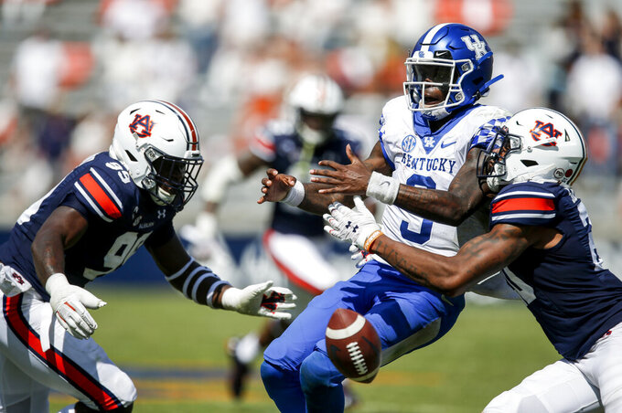 Kentucky quarterback Terry Wilson (3) fumbles the ball as he is tackled by Auburn defensive back Jamien Sherwood (20) and defensive end T.D. Moultry (99) during the fourth quarter of an NCAA college football game on Saturday, Sept. 26, 2020, in Auburn, Alabama. (AP Photo/Butch Dill)