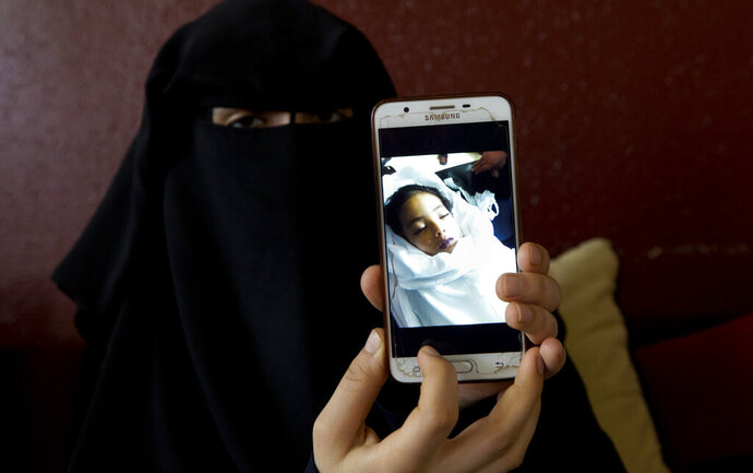 In this Monday, May 27, 2019 photo, Muna Awad, mother of 5-year-old Aisha al-Loulu, shows a photo of her daughter while in a Jerusalem hospital, at the family home in Bureij refugee camp in central Gaza Strip. Instead of a family member, Israeli authorities had approved a stranger to escort Aisha from the blockaded Gaza Strip to the east Jerusalem hospital. As her condition deteriorated, the child was returned to Gaza unconscious. One week later, she was dead. (AP Photo/Hatem Moussa)