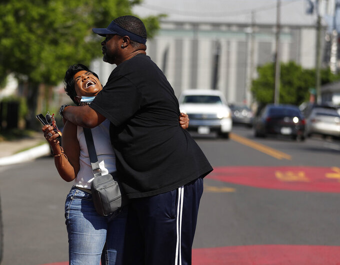 Ceci Munoz reacts with Dennis Glenn at Yates High School as they learn the guilty verdict on all counts in the murder trial of former Minneapolis police Officer Derek Chauvin in the death of George Floyd, Tuesday, April 20, 2021, in Houston. A jury convicted Chauvin today on murder and manslaughter charges. (Karen Warren/Houston Chronicle via AP)