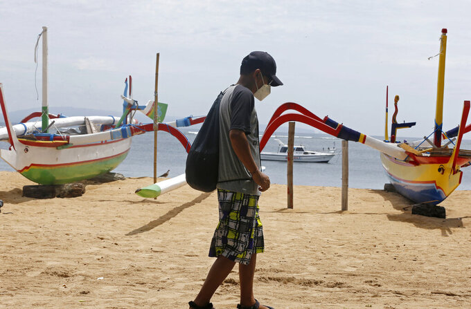 A man wearing a face mask to help curb the spread of coronavirus outbreak walks at a beach in Bali, Indonesia on Saturday, Dec. 5, 2020. (AP Photo/Firdia Lisnawati)