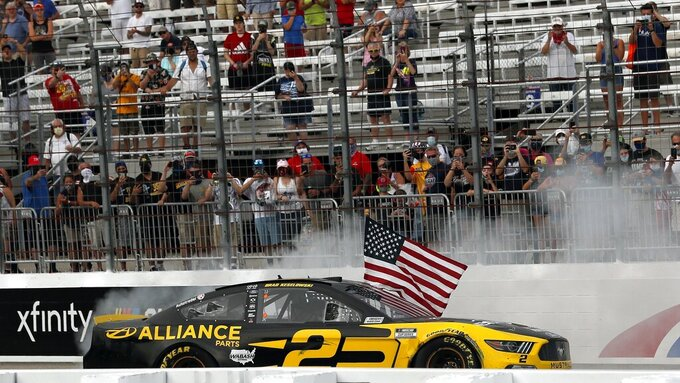 Driver Brad Keselowski celebrates with a burnout and the American flag after winning during a NASCAR Cup Series auto race, Sunday, Aug. 2, 2020, at the New Hampshire Motor Speedway in Loudon, N.H. (AP Photo/Charles Krupa)