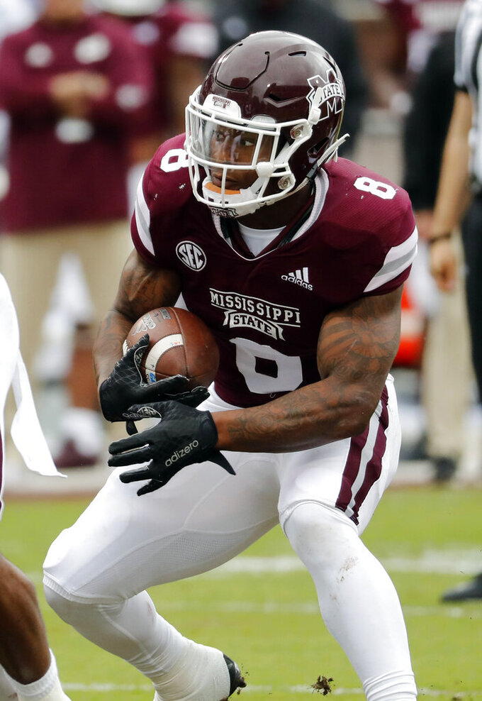 In this April 13, 2019, file photograph, Mississippi State running back Kylin Hill (8) fakes as he runs upfield against the defense during the team's spring NCAA college football game in Starkville, Miss., Saturday, April 13, 2019. Hill, who was injured for part of the 2018 season, is fully recovered and expected to play an important part in Mississippi State's offense. (AP Photo/Rogelio V. Solis, File)
