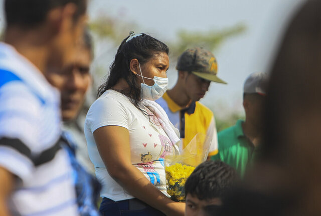 A woman wears a mask against the spread of COVID-19 disease, as she attends a funeral at the Central cemetery of Managua, Nicaragua, Monday, May 11, 2020. President Daniel Ortega's government has stood out for its refusal to impose measures to halt the new coronavirus for more than two months since the disease was first diagnosed in Nicaragua. Now, doctors and family members of apparent victims say, the government has gone from denying the disease's presence in the country to actively trying to conceal its spread. (AP Photo/Alfredo Zuniga)