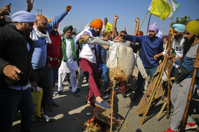 Protesting farmers burn an effigy of Indian Prime Minister Narendra Modi on a highway, refusing to move ahead unless they're allowed to proceed to their place of choice to protest, at the Delhi-Haryana state border, India, Saturday, Nov. 28, 2020. Thousands of farmers in and around the Indian capital on Saturday pressed on with their protest against agricultural legislation they said could devastate crop prices, while the government sought talks with their leaders. (AP Photo/Altaf Qadri)