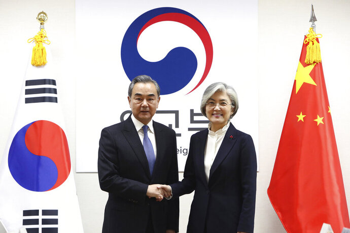 South Korea Foreign Minister Kang Kyung-wha, right, shakes hands with Chinese Foreign Minister Wang Yi  during their meeting at foreign ministry on Wednesday, Dec. 4, 2019 in Seoul, South Korea. Wang Yi arrived in Seoul for talks with his counterpart on his first trip here since bilateral ties soured in 2016 over the installation of a U.S. missile defense system in South Korea. (Chung Sung-Jun/Pool Photo via AP)