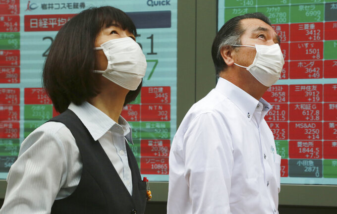 People walk by an electronic stock board of a securities firm in Tokyo, Monday, June 28, 2021. Asian stock markets declined Monday after Wall Street hit a new high as investors looked ahead to manufacturing indicators from Japan, China and South Korea.(AP Photo/Koji Sasahara)