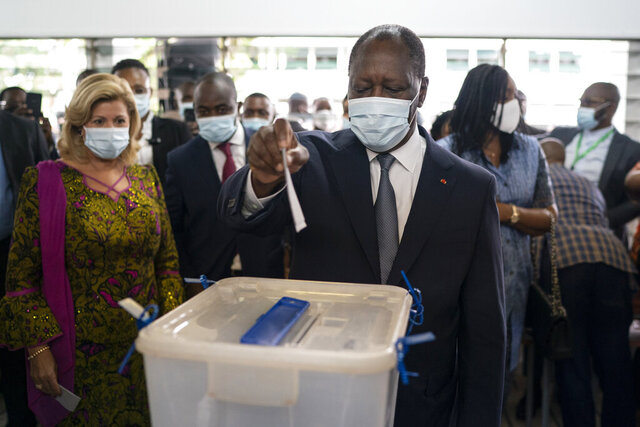 Ivory Coast President Alassane Ouattara casts his vote as his wife Dominique Ouattara, left, looks on at a polling station during presidential elections in Abidjan, Ivory Coast, Saturday, Oct. 31, 2020.  Tens of thousands of security forces are deployed across Ivory Coast on Saturday as the leading opposition parties boycotted the election, calling President Ouattara's bid for a third term illegal. (AP Photo/Leo Correa)
