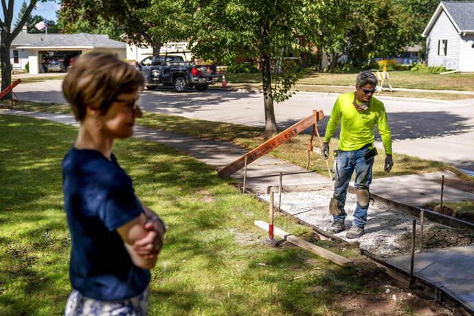 Trisha Kostelny, left, who runs Fischer Ulman Construction with her husband, John, right, looks over their sidewalk concrete project in Appleton, Wis., Aug. 18, 2020. The couple are struggling to find workers. The President Donald Trump administration argues the problem is that the government has been too generous with laid-off workers. But to Trisha Kostelny, the problem is that workers need even more help from the government. (AP Photo/David Goldman)