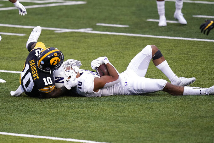 Northwestern linebacker Jeremiah McDonald intercepts a pass in front of Iowa running back Mekhi Sargent, left, during the second half of an NCAA college football game, Saturday, Oct. 31, 2020, in Iowa City, Iowa. (AP Photo/Charlie Neibergall)
