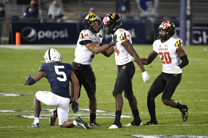 Maryland defensive back Kenny Bennett (24) celebrates with Nick Cross (3) and Antwaine Richardson (20) after intercepting a pass intended for Penn State wide receiver Jahan Dotson (5) in the fourth quarter of an NCAA college football game in State College, Pa., Saturday, Nov. 7, 2020. (AP Photo/Barry Reeger)