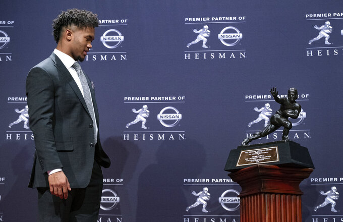 Oklahoma quarterback Kyler Murray, winner of the Heisman Trophy, looks at the award Saturday, Dec. 8, 2018, in New York. (AP Photo/Craig Ruttle)