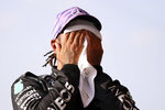 Mercedes driver Lewis Hamilton of Britain wipes his face after clocking the fastest time in the qualifying session ahead of Sunday's British Formula One Grand Prix, at the Silverstone circuit, in Silverstone, England, Friday, July 16, 2021. (Lars Baron/Pool photo via AP)