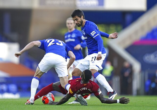 Everton's Seamus Coleman, left, and Everton's Andre Gomes challenge Liverpool's Sadio Mane during the English Premier League soccer match between Everton and Liverpool at Goodison Park in Liverpool, England, Sunday, June 21, 2020. (AP photo/Jon Super, Pool)