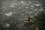 In this Sunday, Jan. 19, 2020, file photo, a man swims laps in a partially-frozen lake at a public park in Beijing. According to local folk wisdom, swimming in icy water in winter is good for one's health. (AP Photo/Mark Schiefelbein, File)