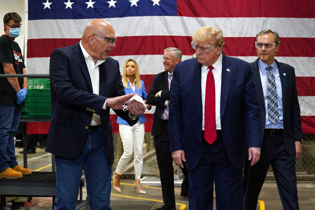 President Donald Trump participates in a tour of a Honeywell International plant that manufactures personal protective equipment, Tuesday, May 5, 2020, in Phoenix, with Tony Stallings, vice president of Integrated Supply Chain at Honeywell. (AP Photo/Evan Vucci)