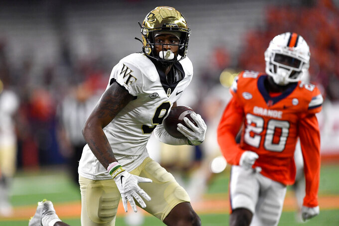 Wake Forest wide receiver A.T. Perry (9) runs for a touchdown in front of Syracuse defensive back Darian Chestnut (20) during the second half of an NCAA college football game in Syracuse, N.Y., Saturday, Oct. 9, 2021. (AP Photo/Adrian Kraus)