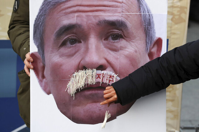 In this Dec. 13, 2019, photo, a protester plucks face mustache from a picture of U.S. Ambassador to South Korea Harry Harris during a rally to denounce the United States' policies against North Korea near the U.S. embassy in Seoul, South Korea. Harris has some unusual explanations for the harsh criticism he's faced in his host country. His mustache, maybe? Or a Japanese ancestry that raises unpleasant reminders of Japan's former colonial domination of Korea? (Lee Yong-hwan/Newsis via AP)