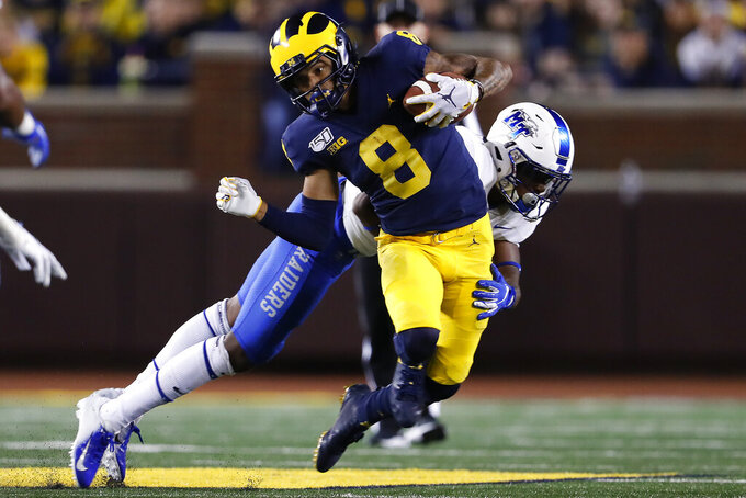 Michigan wide receiver Ronnie Bell (8) breaks the tackle of Middle Tennessee safety Decorian Patterson during the second half of an NCAA college football game in Ann Arbor, Mich., Saturday, Aug. 31, 2019. (AP Photo/Paul Sancya)