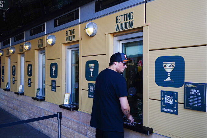 Sports betting windows officially open as the Arizona Diamondbacks partner with Caesars Entertainment setting up temporary sports betting windows at the Diamondbacks' Chase Field, the baseball home of the Diamondbacks baseball team, Thursday, Sept. 9, 2021, in Phoenix. The on-site sports betting permanent home just outside Chase Field will be opened in the coming months. (AP Photo/Ross D. Franklin)