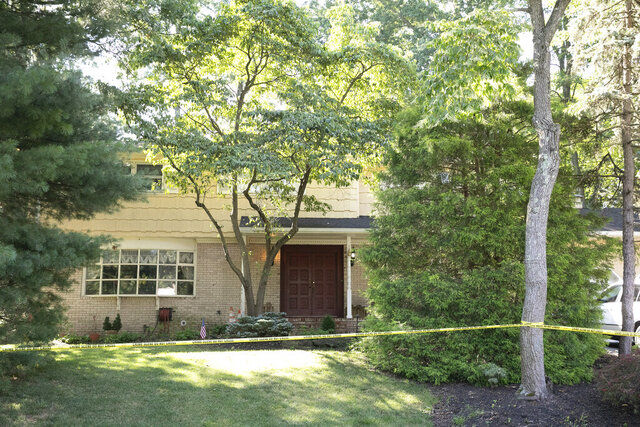 Crime scene tape surrounds the home of U.S. District Judge Esther Salas, Monday, July 20, 2020, in North Brunswick, N.J. A gunman posing as a delivery person shot and killed Salas' 20-year-old son and wounded her husband Sunday evening at their New Jersey home before fleeing, according to judiciary officials.  (AP Photo/Mark Lennihan)