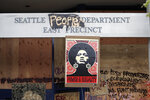 A 1970's-era poster of activist Angela Davis hangs at a boarded up and closed Seattle police precinct Sunday, June 21, 2020, in Seattle, where streets are blocked off in what has been named the Capitol Hill Occupied Protest zone. Police pulled back from several blocks of the city's Capitol Hill neighborhood near the Police Department's East Precinct building earlier in the month after clashes with people protesting the death of George Floyd, a Black man who died after being restrained by Minneapolis police officers on May 25. (AP Photo/Elaine Thompson)