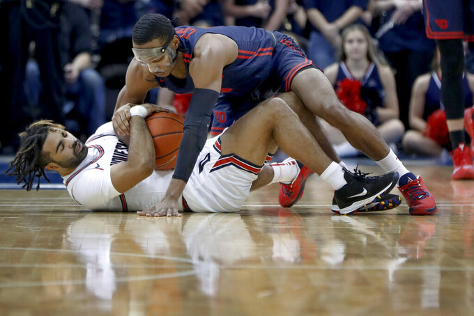 Duquesne's Sincere Carry, bottom, and Dayton's Jalen Crutcher scramble for the ball during the first half of an NCAA college basketball game Wednesday, Jan. 29, 2020, in Pittsburgh. (AP Photo/Keith Srakocic)