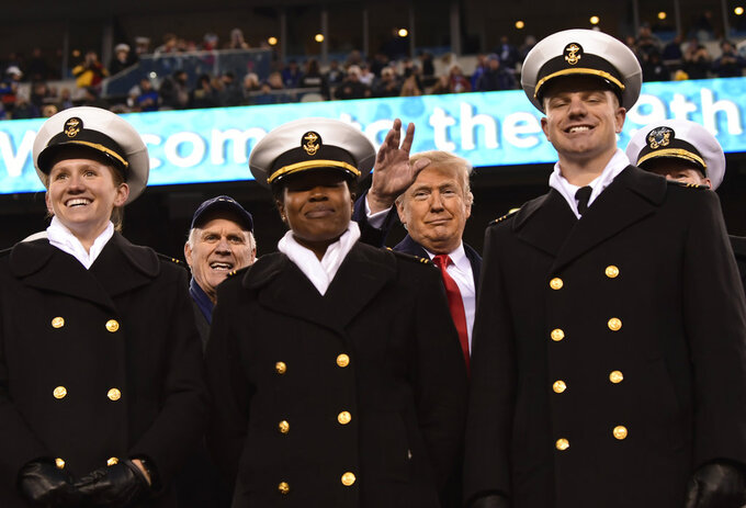 President Donald Trump, background center, standing with Navy Secretary Richard Spencer, second from left, and Naval Academy Superintendent Vice Adm. Ted Carter, background right, watch the second half of the Army-Navy football game in Philadelphia, Saturday, Dec. 8, 2018. (AP Photo/Susan Walsh)