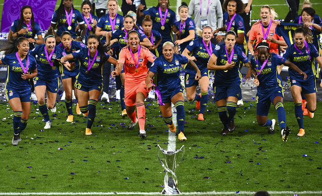 Lyon players pose with trophy after winning the Women's Champions League final soccer match between Wolfsburg and Lyon at the Anoeta stadium in San Sebastian, Spain, Sunday, Aug. 30, 2020. Lyon won the match 1-3. (Gabriel Buoys/Pool via AP)