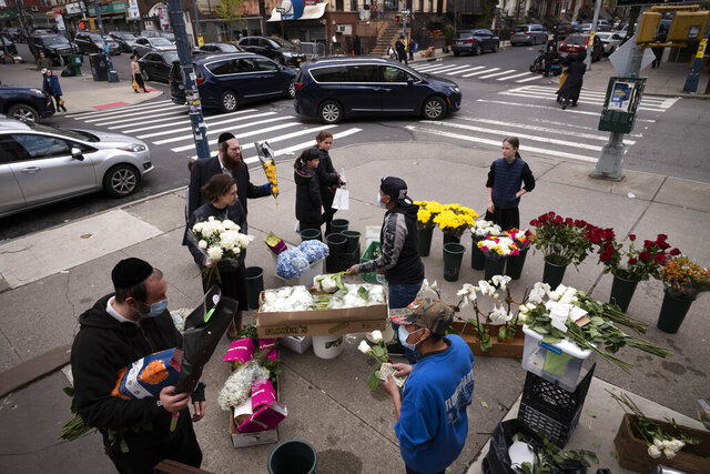 People buy flowers from a sidewalk flower stand on the first day of Passover, Wednesday, April 8, 2020 in the Williamsburg neighborhood of New York during the coronavirus pandemic. (AP Photo/Mark Lennihan)