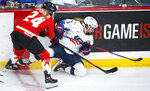 Canada's Natalie Spooner, left, checks United States' Savannah Harmon during the second period of the IIHF hockey women's world championships title game in Calgary, Alberta, Tuesday, Aug. 31, 2021. (Jeff McIntosh/The Canadian Press via AP)