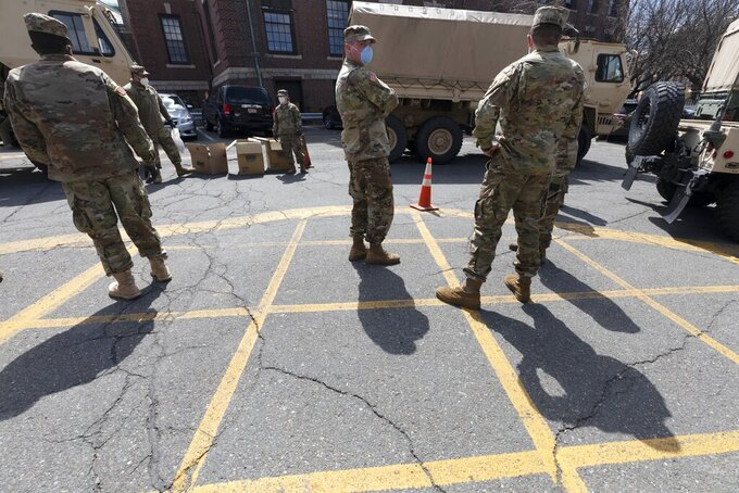 FILE — Massachusetts National Guard soldiers help with logistics in this Friday, April 17, 2020 file photo, at a food distribution site outside City Hall, in Chelsea, Mass. Mass. Gov. Charlie Baker on Monday, Sept. 13, 2021, activated the state's National Guard to help with busing students to school as districts across the country struggle to hire enough drivers. (AP Photo/Michael Dwyer, File)