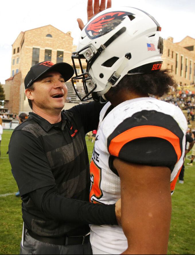 Oregon State head coach Jonathan Smith congratulates Doug Taumoelau (42) following the team's overtime win against Colorado during an NCAA football game, Saturday, Oct. 27, 2018, in Boulder, Colo. (AP Photo/Jack Dempsey)