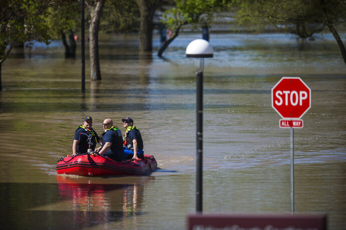 Law enforcement officers patrol downtown Midland, Mich. in a rescue boat Thursday, May 21, 2020. Severe flooding was caused by dam failures upstream. (Katy Kildee/Midland Daily News via AP)