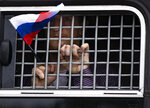 A detained protester holds a Russian flag while looking out of a police bus window during a march in Moscow, Russia, Wednesday, June 12, 2019. Police and hundreds of demonstrators are facing off in central Moscow at an unauthorized march against police abuse in the wake of the high-profile detention of a Russian journalist. More than 20 demonstrators have been detained, according to monitoring group. (AP Photo/Alexander Zemlianichenko)